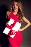 Sexy blonde Frau, die einen Kasten mit einem Geschenk, werfend im Studio hält auf Stockfotos