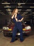 Sexy blonde Frau, die in einer Autogarage aufwirft Lizenzfreies Stockfoto