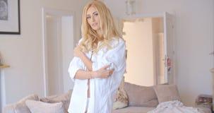 Sexy blonde Frau, die ihr Hemd aufknöpft Lizenzfreies Stockbild