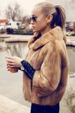 Sexy blonde Frau, die luxuriösen Pelzmantel und -Sonnenbrille trägt Lizenzfreies Stockfoto