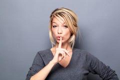 Sexy blonde Frau, die Ruhe mit Index auf Lippen fordert lizenzfreie stockbilder