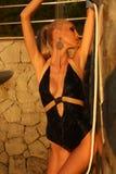 Sexy blonde Frau im Bikini, der auf Sonnenuntergangstrand aufwirft Lizenzfreie Stockfotos