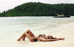 Sexy blonde Frau im Bikini, der auf Strand in Thailand sich entspannt Lizenzfreie Stockfotos