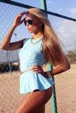Sexy blonde Frau im blauen Kleid auf dem Strand Stockfotografie