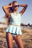 Sexy blonde Frau im blauen Kleid auf dem Strand Stockbilder