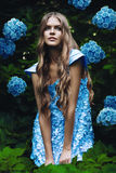 Sexy blonde Frau im blauen Kleid mit Blumen Stockbild