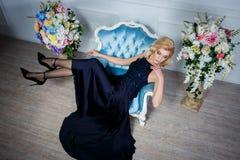 Sexy blonde Frau im dunkelblauen Kleid auf Stuhl Stockfoto