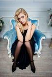 Sexy blonde Frau im dunkelblauen Kleid auf Stuhl Stockfotos