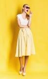Sexy blonde Frau im gelben Rock mit Lutscher Lizenzfreies Stockbild