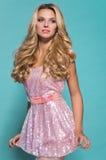 Sexy blonde Frau im kurzen rosa Kleid Stockfotografie