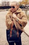 Sexy blonde Frau im luxuriösem Pelzmantel und -Sonnenbrille Lizenzfreies Stockbild