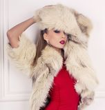 sexy blonde Frau im roten Kleid mit Pelzmantel Lizenzfreies Stockbild