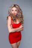 Sexy blonde Frau im roten Mode-Kleid auf grauem Hintergrund Stockbild
