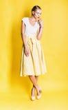 Sexy blonde Frau im schönen gelben Rock Stockbilder