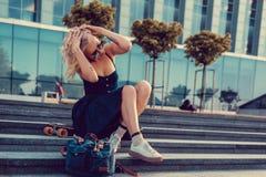 Sexy blonde Frau im schwarzen Kleid, das mit longboard aufwirft Lizenzfreies Stockbild