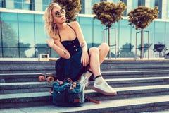 Sexy blonde Frau im schwarzen Kleid, das mit longboard aufwirft Stockfotos