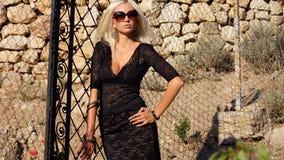 Sexy blonde Frau im schwarzen Kleid mit Sonnenbrille Stockbild