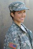 Sexy blonde Frau mit USA-Flagge auf der Armeeuniform, die an der grauen Wand aufwirft Lizenzfreies Stockfoto