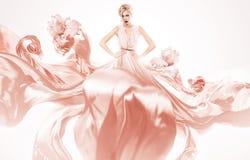 Sexy blonde Frau, wenn rotes Kleid geflogen wird Lizenzfreies Stockbild