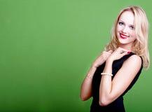 Sexy blonde Geschäftsfrau auf grünem Hintergrund Stockbild