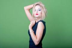 Sexy blonde Geschäftsfrau auf grünem Hintergrund Stockfotografie