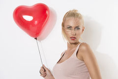 blonde girl  with balloon and hair on the face Stock Image