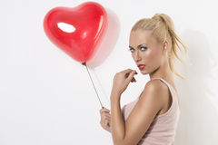 Sexy blonde girl with balloon and hand near the mouth Stock Photos
