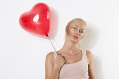 blonde girl with balloon and hand near the shoulder Royalty Free Stock Images