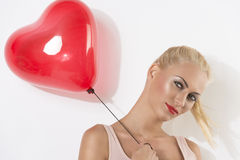 Sexy blonde girl with balloon smiles. Sexy blonde girl with heart shaped balloon, she looks in to the lens and smiles Royalty Free Stock Photos