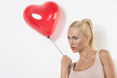 Sexy blonde girl with balloon turned at right. Sexy blonde girl with heart shaped balloon, she is turned of three quarters at right and looks in to the lens Royalty Free Stock Image
