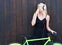 Sexy blonde girl in black binding outfit listening to music and eating ice cream on a summer day next to a bright bike. Fixed. Street style Royalty Free Stock Photography