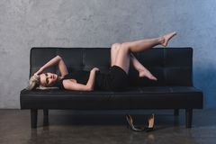 Sexy blonde girl in black dress lying on sofa and looking. At camera royalty free stock photo