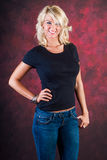 Sexy blonde girl fashion model in blue jeans. Sexy blonde girl / woman / female fashion model wearing blue jeans and a black t shirt against a red studio Stock Photo