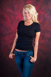 Sexy blonde girl fashion model in blue jeans. Sexy blonde girl / woman / female fashion model wearing blue jeans and a black t shirt against a red studio Royalty Free Stock Photography