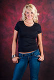 Blonde girl fashion model in blue jeans. Blonde girl / woman / female fashion model wearing blue jeans and a black t shirt against a red studio background / royalty free stock photo