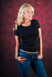 Sexy blonde girl fashion model in blue jeans. Sexy blonde girl / woman / female fashion model wearing blue jeans and a black t shirt against a red studio Royalty Free Stock Image