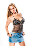 Sexy blonde girl / fashion model. Sexy blonde woman in trendy fashion clothing. Fashion model girl showing cleavage / breasts. Blue denim short mini skirt Royalty Free Stock Photo