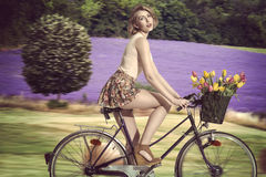 blonde girl going on the bicycle on field Stock Photo