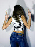Sexy blonde girl in jeans and striped t-shirt, turned his back and raised both hands up, showing middle finger Royalty Free Stock Photos