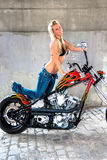 Sexy Blonde Girl on Motorcycle. Sexy blonde woman swimsuit fashion model  with black top and blue jeans laying on top of a motorbike chopper with flames Stock Photography