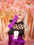 Charming plump blonde woman in a purple corset with long gloves holds a paper Cup of takeaway coffee. Sexy blonde girl with plump body holds a paper cup of tea royalty free stock image