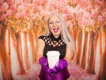 Charming plump blonde woman in a purple corset with long gloves holds a paper Cup of takeaway coffee. Sexy blonde girl with plump body holds a paper cup of tea stock photo