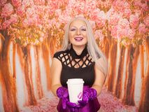 Charming plump blonde woman in a purple corset with long gloves holds a paper Cup of takeaway coffee. Sexy blonde girl with plump body holds a paper cup of tea stock photography