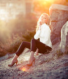 Sexy blonde girl sitting near big rock on hill Royalty Free Stock Images