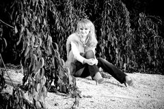 Sexy blonde girl sitting under tree in park Stock Photography