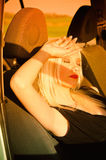 Sexy blonde girl sleeping in the car. Sunset time Stock Images