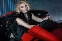 Sexy blonde girl in sports car. Sexy blonde woman posing in red sports car Royalty Free Stock Image