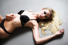 Sexy blonde girl in underwear lying on floor. Studio shot Royalty Free Stock Photo