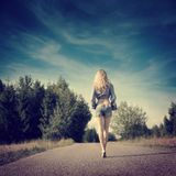 Blonde Girl Walking Away. Full Length Photo of Blonde Girl Walking Away. Toned Instagram Styled Photo with Copy Space. Trendy Street Style stock images