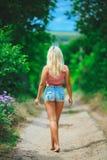 Girl walking barefoot. Blonde girl walking barefoot in summer royalty free stock photos